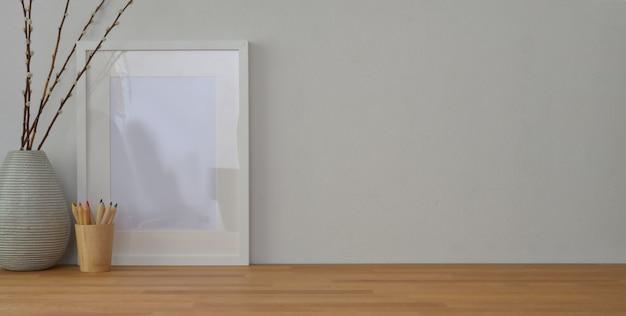 Lugar de trabajo con marco simulado y material de oficina en mesa de madera y pared blanca