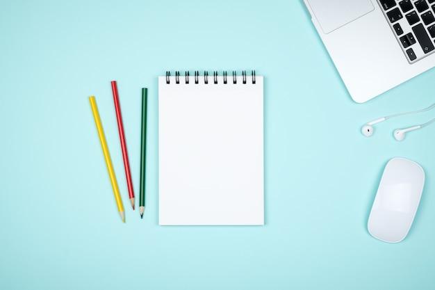 Lugar de trabajo mínimo con computadora portátil y bloc de notas en blanco
