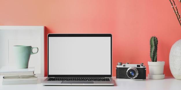 Lugar de trabajo mínimo con computadora portátil con pantalla en blanco abierta