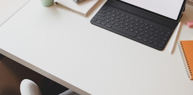 Lugar de trabajo mínimo con tableta de pantalla en blanco y espacio de copia