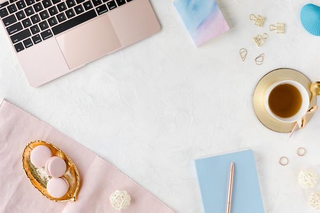 Lugar de trabajo moderno blanco con laptop y taza de té.