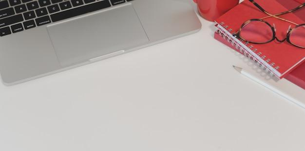 Lugar de trabajo moderno con computadora portátil y cuaderno rojo con otros suministros de oficina