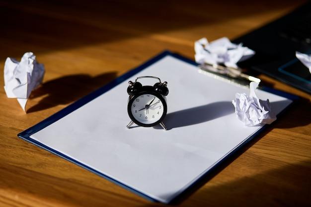 Lugar de trabajo moderno, escritorio de oficina de madera con luz dura, luz solar con reloj, hoja de papel, computadora portátil, cuaderno, bolas de papel arrugadas, cambie su mentalidad, plan b, tiempo para establecer nuevas metas, negocios