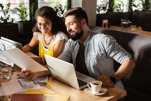 Lugar de trabajo moderno. gente agradable e inteligente hablando entre sí mientras trabaja en sus computadoras portátiles