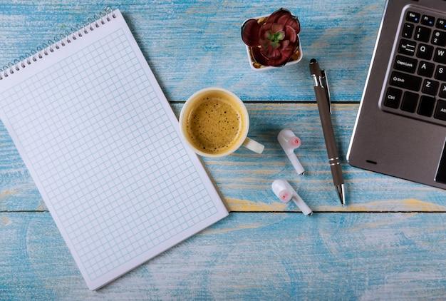 Lugar de trabajo moderno de oficina con bloc de notas, auriculares, gafas, bolígrafo y taza de café en el teclado de la computadora portátil