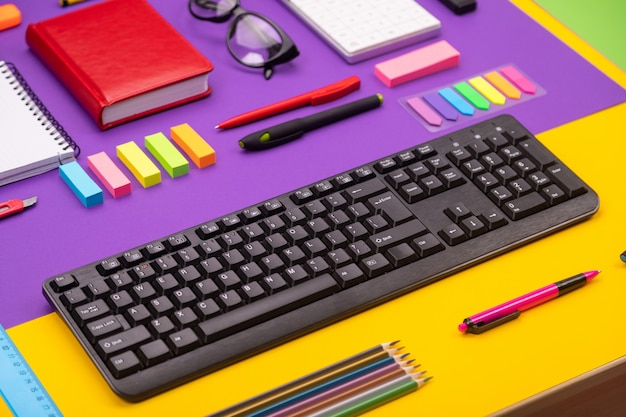 Lugar de trabajo moderno con teclado, diario, lápices, bolígrafos y gafas sobre fondo naranja-púrpura. vista superior