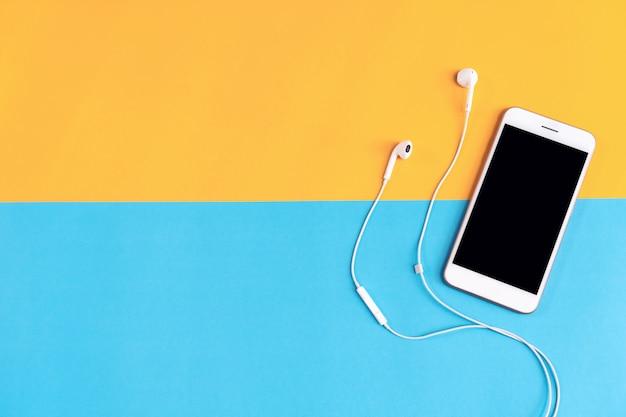 Lugar de trabajo moderno con teléfono inteligente colocado en el fondo en colores pastel