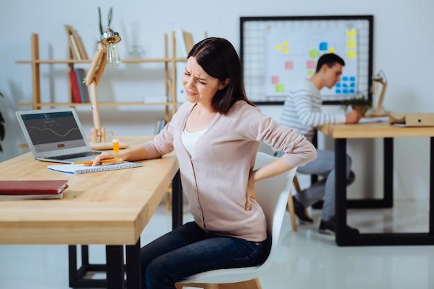 En el lugar de trabajo. mujer molesta haciendo muecas por el dolor y tocando la espalda mientras está sentada en posición semi