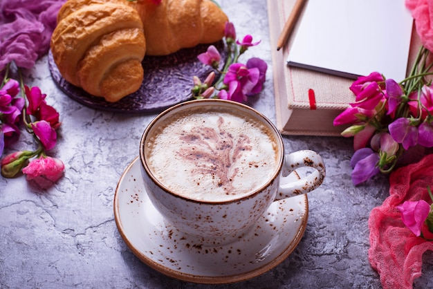 Lugar de trabajo de las niñas. café, croissants, flor y cuaderno. vista superior
