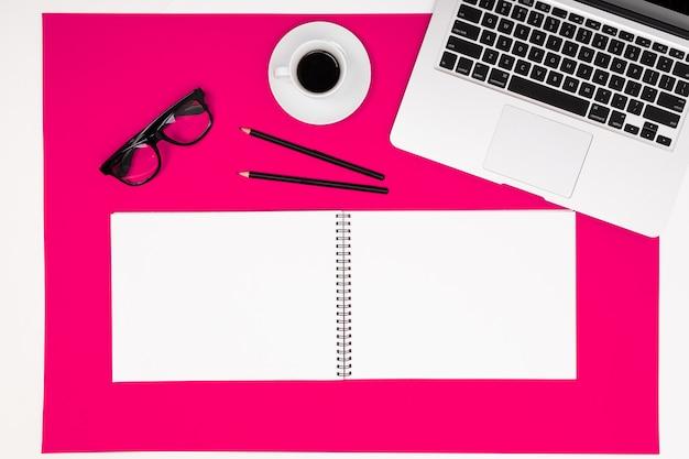 Lugar de trabajo de oficina arriba con bloc de notas con maqueta, computadora portátil y lápiz sobre superficie rosa