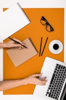 Lugar de trabajo de oficina con cuadernos con maqueta, computadora portátil y lápiz sobre superficie naranja