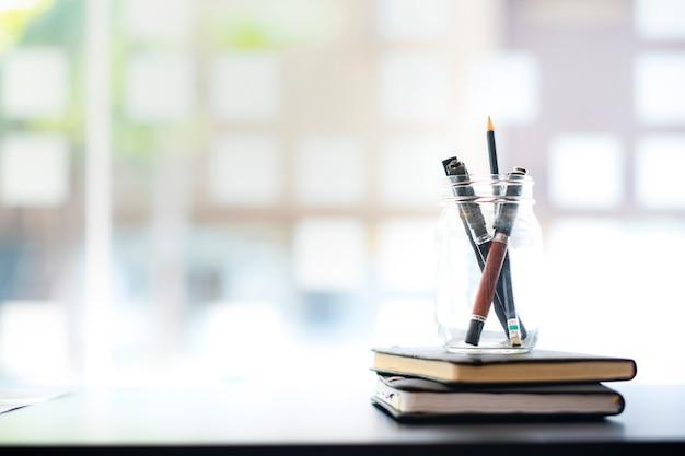 Lugar de trabajo en la oficina de la empresa, bolígrafo y libros sobre la mesa de trabajo.