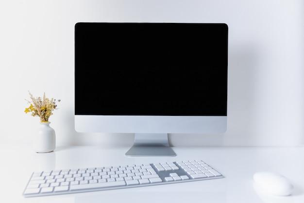 Lugar de trabajo de oficina limpio y minimalista con computadora de escritorio. vista frontal de la pc, teléfono celular, papeles y teclado numérico en la mesa blanca limpia