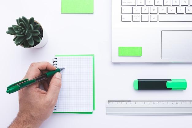Lugar de trabajo en la oficina con la mano escribiendo en el cuaderno, portátil y suministros de oficina verde en un escritorio blanco.