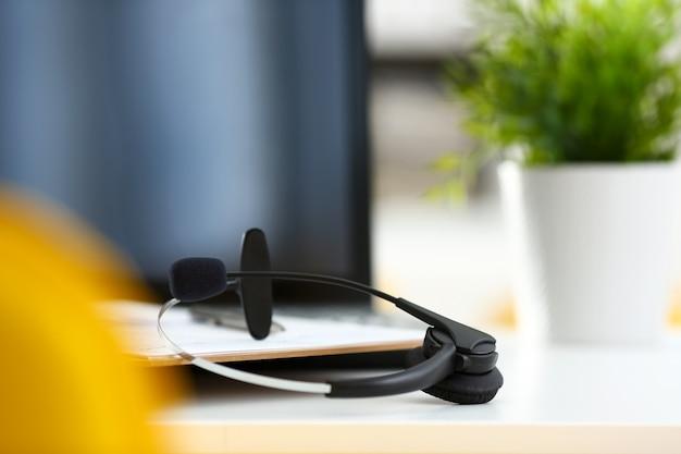 Lugar de trabajo de oficina remota vacía con laptop y auriculares