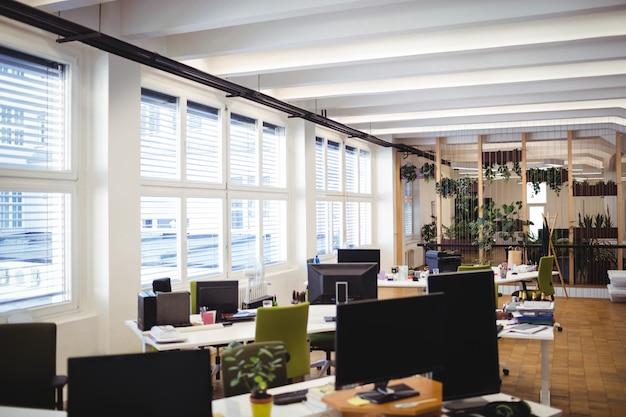 El lugar de trabajo de oficina vacía con una mesa, una silla y el ordenador
