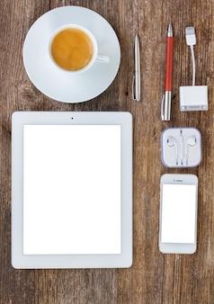 Lugar de trabajo de oficina de vista superior. juego de tableta, teléfono y taza de café en la mesa de madera, copie el espacio en la pantalla