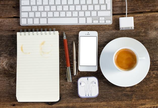 Lugar de trabajo de oficina de vista superior. teclado con teléfono, café y portátil en la mesa de madera