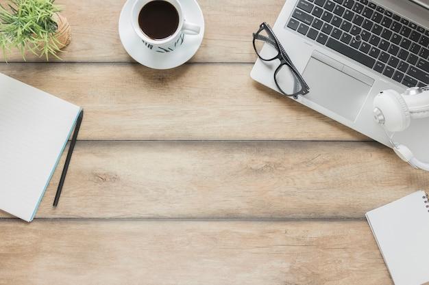 Lugar de trabajo con papelería, dispositivos electrónicos y taza de café en la mesa de madera.