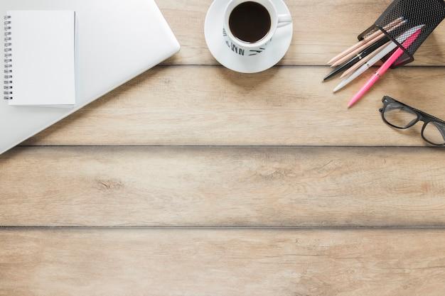 Lugar de trabajo con papelería, laptop y taza de café.