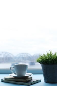Lugar de trabajo con planta, cuadernos y taza de café.