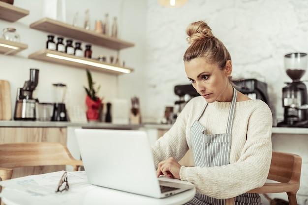 Lugar de trabajo. propietario de café inteligente enfocado sentado en la mesa trabajando en su computadora portátil.