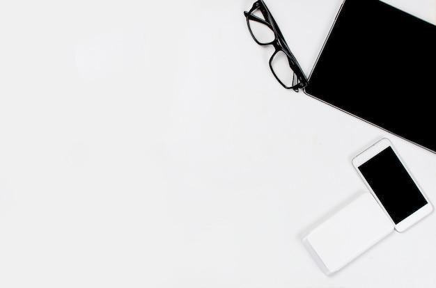 Lugar de trabajo con tableta, teléfono inteligente, bolígrafo, bloc de notas y gafas.