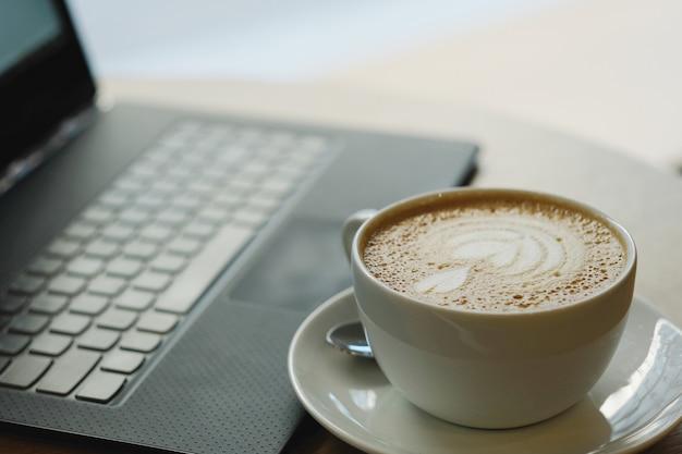 Lugar de trabajo con taza de café y computadora portátil
