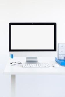 Lugar de trabajo con teclado cerca del monitor, gafas y ratón de la computadora.