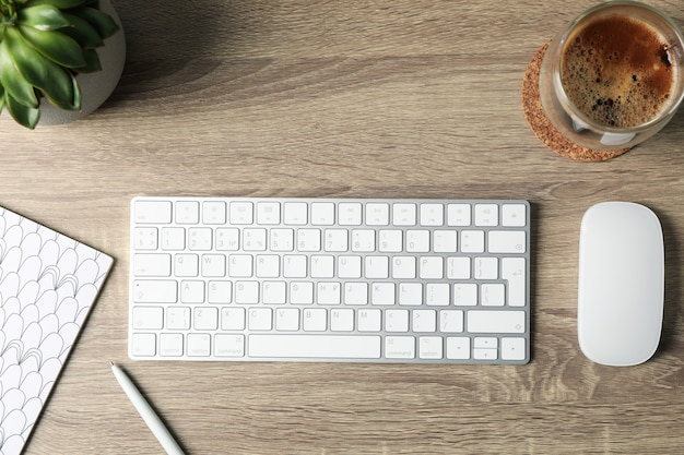 Lugar de trabajo. teclado, mouse, planta, taza de café y cuaderno en madera, vista superior