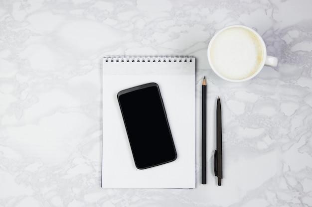 Lugar de trabajo con teléfono, bloc de notas, bolígrafo y una taza de café sobre una mesa de mármol. vista superior, plano, copia espacio