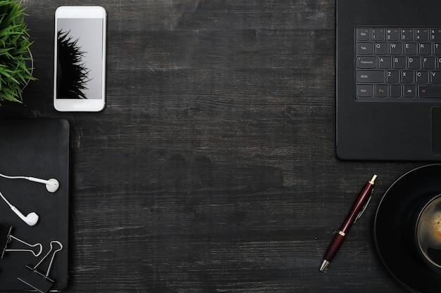 Lugar de trabajo con teléfono inteligente, computadora portátil, en mesa negra. fondo de copyspace vista superior