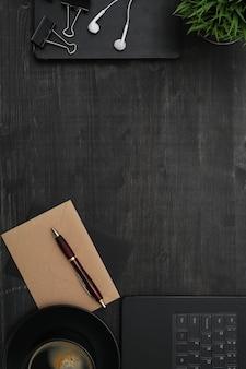 Lugar de trabajo con teléfono inteligente, portátil, en mesa negra. vista superior