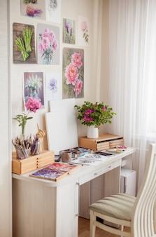 Un lugar de trabajo vacío y acogedor del artista es el lugar para las clases de pasatiempos con ramos de flores y materiales para la creatividad, lápices y pinceles. concepto de inspiración