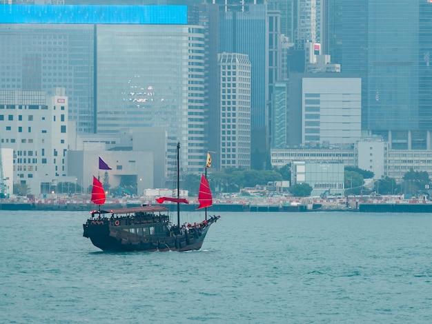 Lugar de viaje popular con velero rojo en el puerto de victoria con la construcción en hong kong