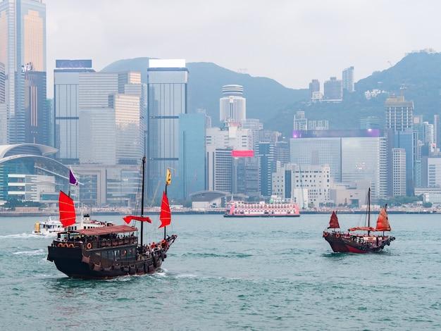 Lugar de viaje popular con veleros rojos en el puerto de victoria con la construcción en hong kong