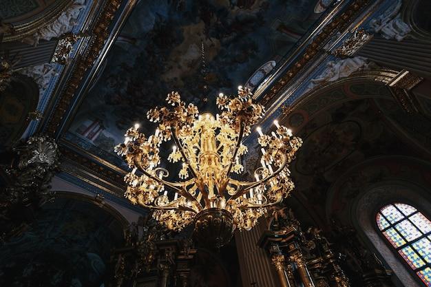 Lujosa lámpara de oro cuelga bajo el techo