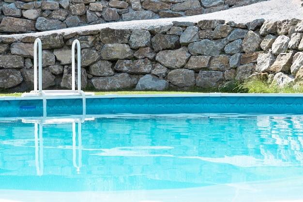 Lujoso estilo de relajación. vista de la piscina turquesa con césped verde y una pared de piedras. concepto de vacaciones, diseño del paisaje, parque acuático, hotel