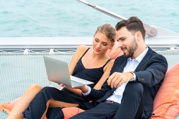 El lujoso y relajante viajero de pareja con un bonito vestido y una suite se sienta en el puf y mira la computadora
