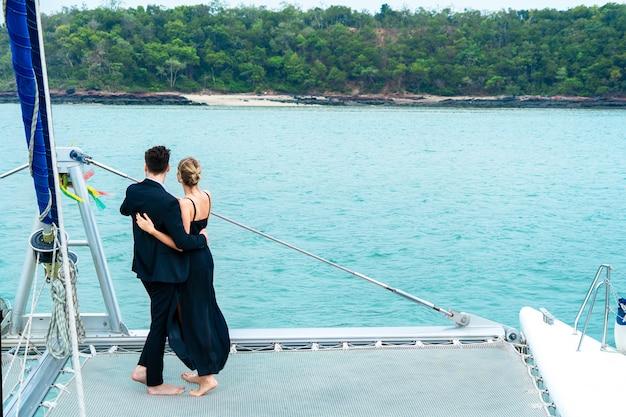 El lujoso y relajante viajero de pareja con un bonito vestido y un traje se colocan en la parte delantera del yate de crucero.