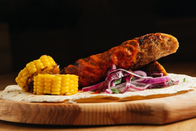 Lula kebab con pan de pita, salsa, maíz asado y cebolla sobre una tabla de madera