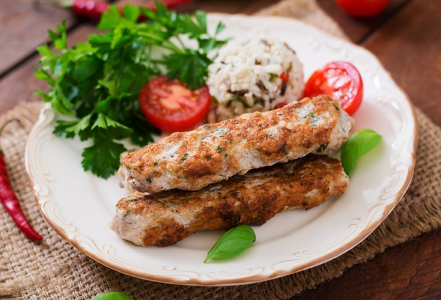 Lula kebab picada de pavo a la parrilla (pollo) con arroz y tomate.