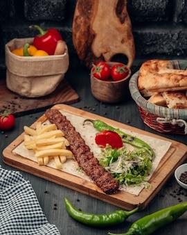 Lula kebab servido con papas fritas, ensalada y pimiento asado