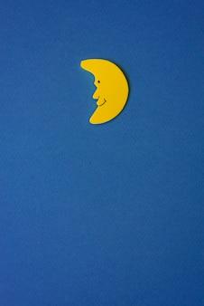 Luna creciente amarilla contra el cielo azul de la noche. documento de solicitud a la derecha. copia espacio