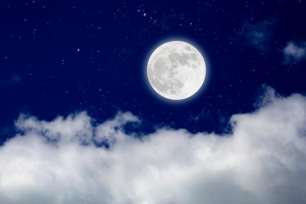 Luna llena con cielo estrellado y nubes.