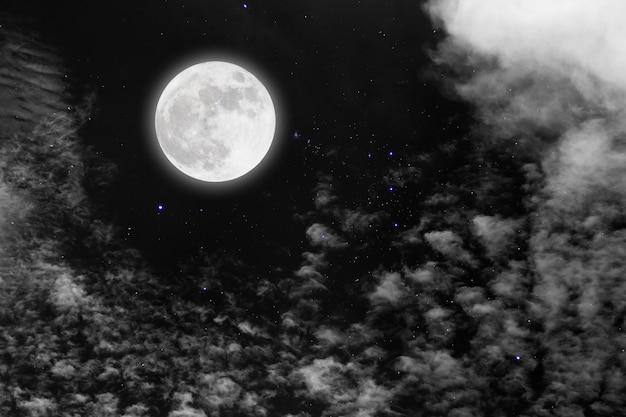 Luna llena con estrellado y nubes.