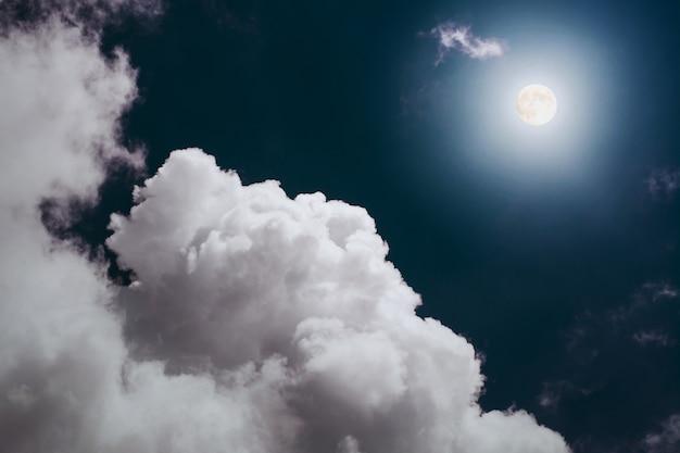 Luna llena con una gran nube esponjosa en el cielo nocturno.