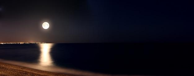 La luna llena hermosa en la playa