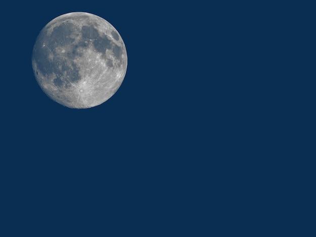Luna llena vista con telescopio sobre azul con espacio de copia