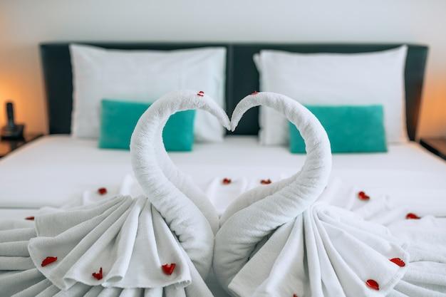 Luna de miel: dos hermosos cisnes hechos de toallas, ubicados en una cama blanca con pasteles de rosas. luna de miel . corazón. cisnes símbolo de amor.